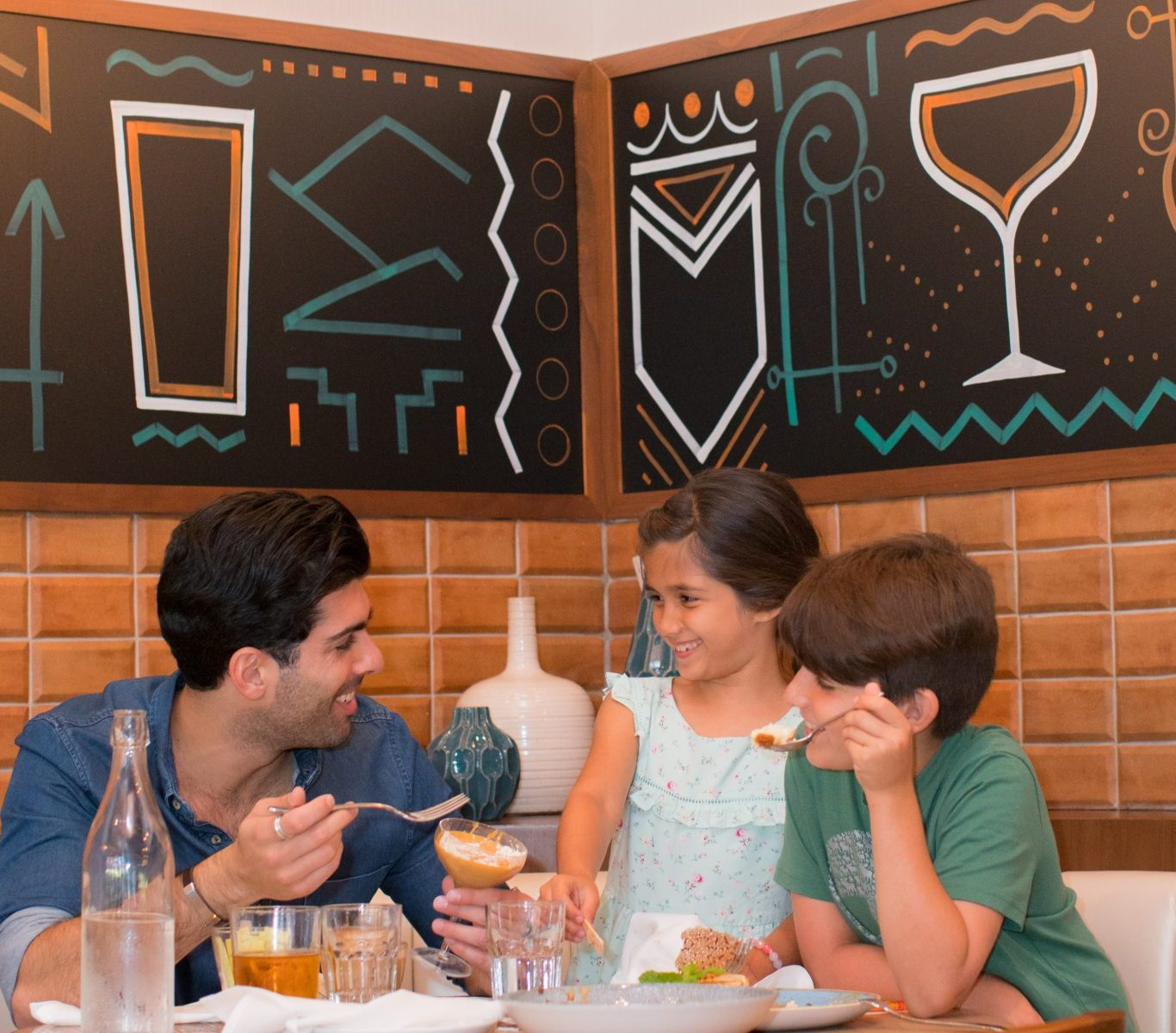 Father and kids eating at table